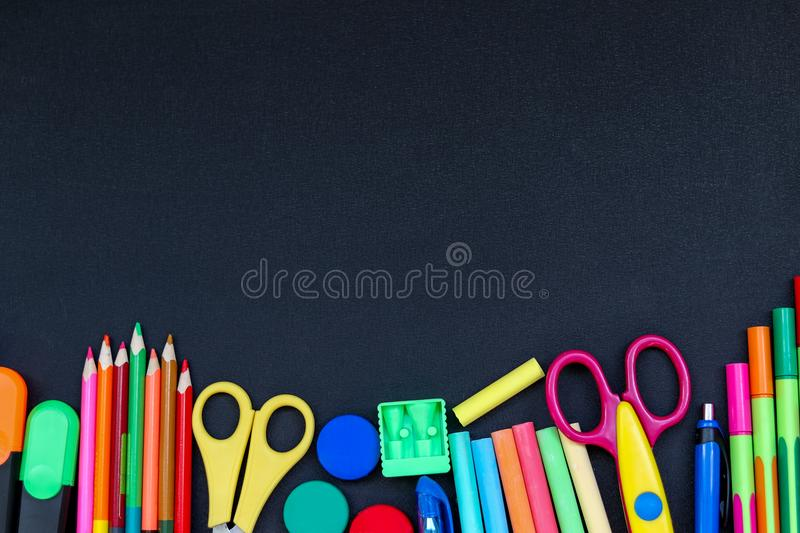 Bright school supplies on blackboard background ready for your design stock photography