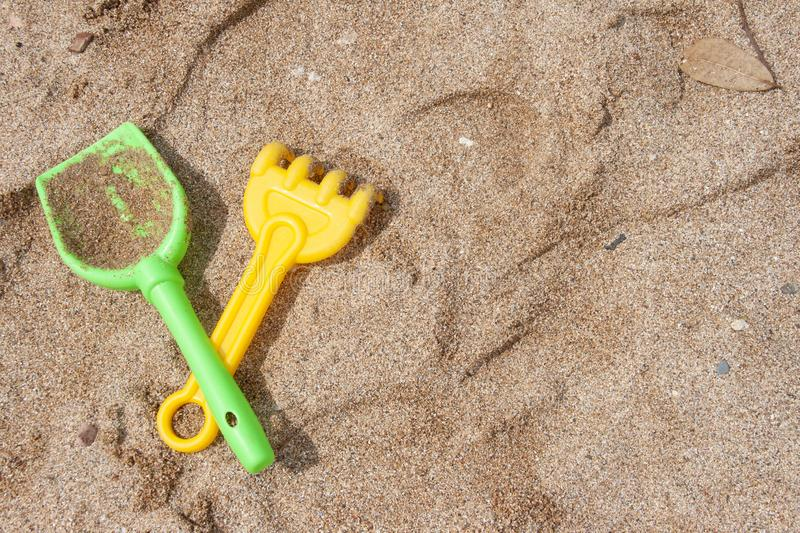 A bright set for playing with sand: a shovel and a rake. Children`s toys for the beach stock image