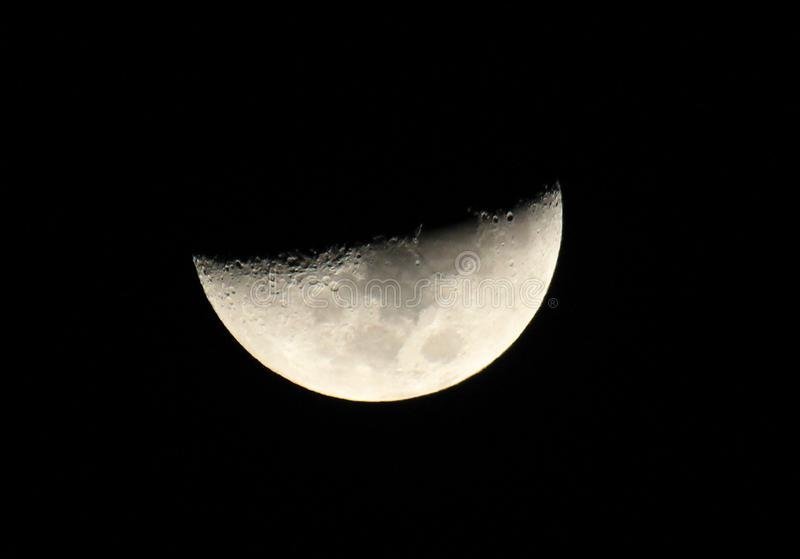 Bright Silver halfmoon in a starless sky closeup. Bright Sliver of a silver half moon surrounded by the dark abyss of night as seen from earth zoomed stock photography