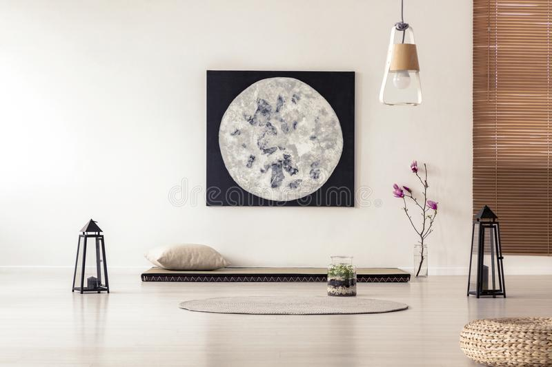 Bright and simple bedroom interior with asian style tatami mat b. Ed, cherry blossom, moon painting on white wall and black lanterns. Real photo royalty free stock photo