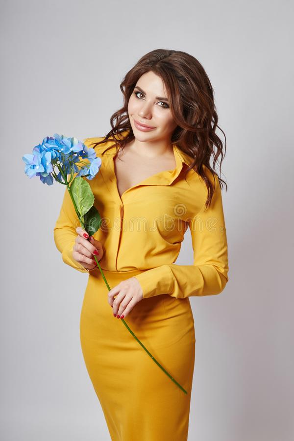 Bright spring portrait of a woman in a yellow skirt and blouse. Long curly hair and beautiful plump lips. Girl with a summer mood. Posing on a light background stock images