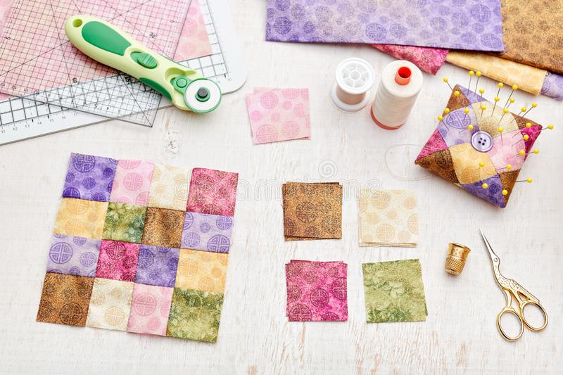 Bright square pieces of fabric, patchwork tools, sewing equipment, traditional quilting royalty free stock photography