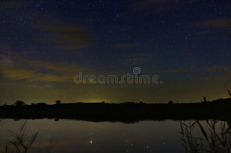 Bright stars with clouds over the river in the night sky. Outer space photographed with long exposure.  royalty free stock photos