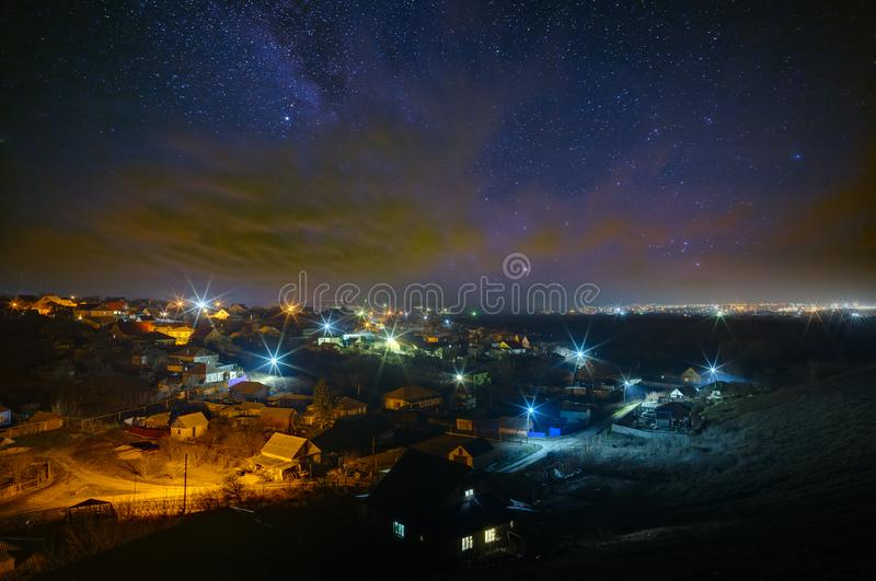 The bright stars of the Milky Way with clouds in the night sky over the city. Light pollution from street lamps.  royalty free stock images