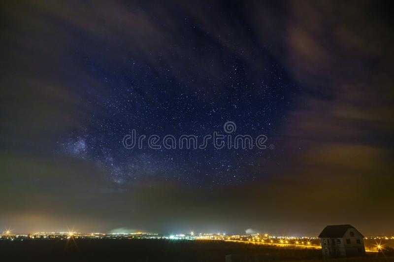 The bright stars of the Milky Way with clouds in the night sky over the city. Light pollution from street lamps.  royalty free stock photos