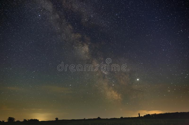 The bright stars of the Milky Way galaxy above the horizon in the night sky. Outer space photographed with long exposure.  stock photos
