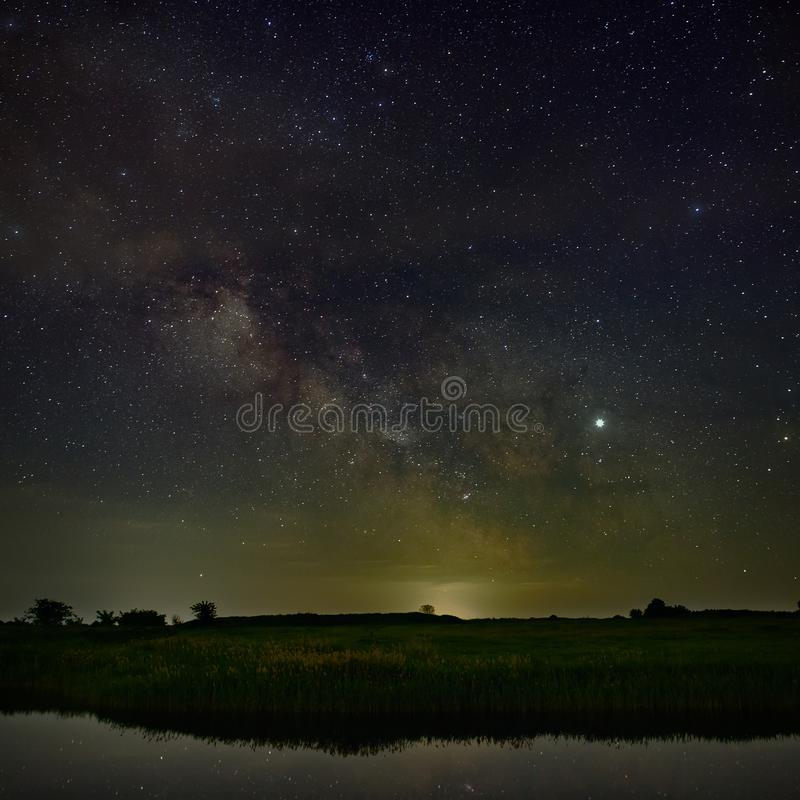 Bright stars of the Milky Way galaxy over the river in the night sky. Outer space photographed with long exposure.  stock photo