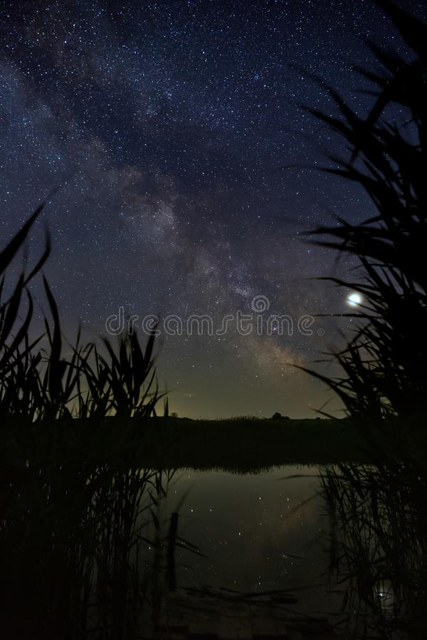 Bright stars of the Milky Way galaxy over the river in the night sky. Outer space photographed with long exposure.  royalty free stock images