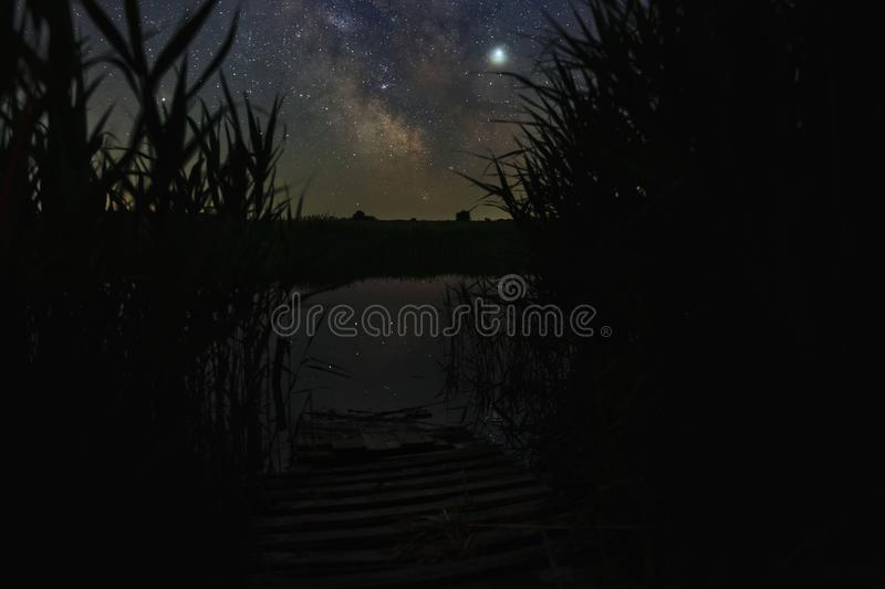 Bright stars of the Milky Way galaxy over the river in the night sky. Outer space photographed with long exposure.  stock photos