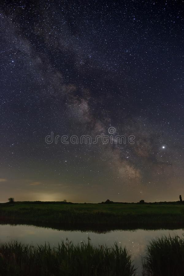 Bright stars of the Milky Way galaxy over the river in the night sky. Outer space photographed with long exposure.  royalty free stock image