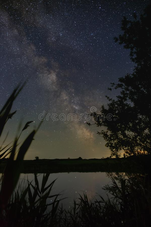 Bright stars of the Milky Way galaxy over the river in the night sky. Outer space photographed with long exposure.  royalty free stock photos