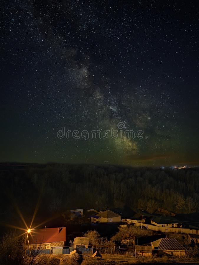 Bright stars of the Milky Way in the night sky over the city. Light pollution from street lamps.  stock images