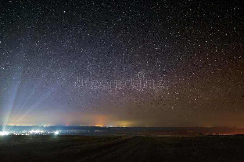 Bright stars of the Milky Way in the night sky over the city. Light pollution from street lamps.  stock photography