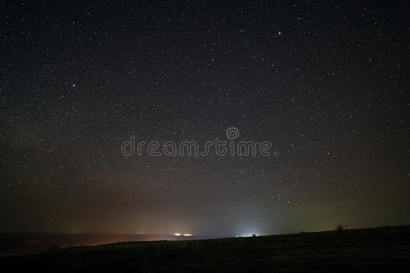 Bright stars in the night sky with lighting from the street lamps of the city. Light pollution.  royalty free stock photography