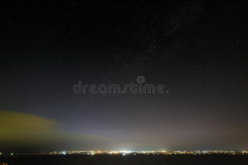 Bright stars in the night sky over the city. Light pollution from street lamps.  stock photo