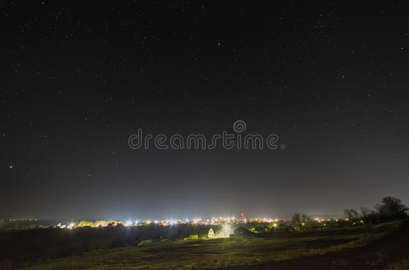 Bright stars in the night sky over the city. Light pollution from street lamps.  stock photos
