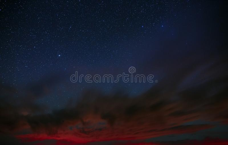 Bright stars shine through the clouds in the night royalty free stock photos