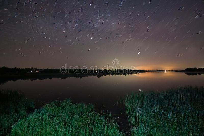 Bright stars shine and fly over a big countryside lake with bushes of bulrush on a warm spring night in the clear dark blue sky royalty free stock images