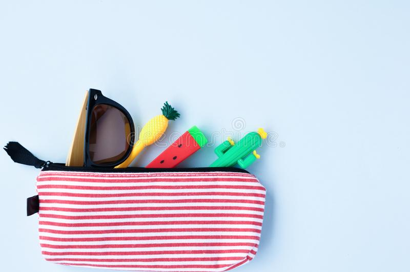 Bright stationery pens in the form of a cactus, watermelon, pineapple in a pencil case and sunglasses on a blue background. Back stock photography