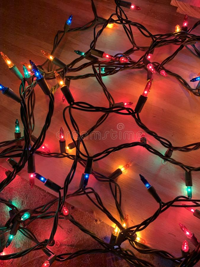 A bright string of Christmas light on the floor. A photo of a lighted string of Christmas lights laying on the floor showing tangles of the cords stock photo