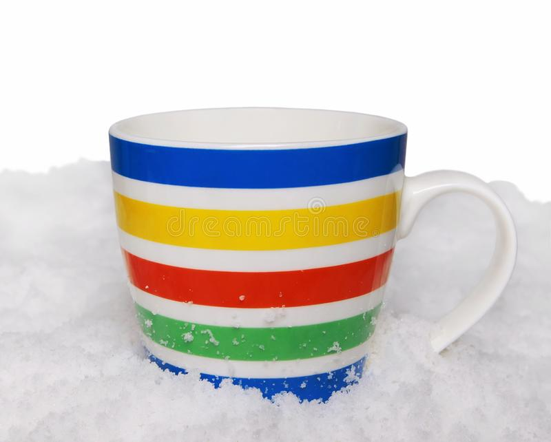 Bright striped mug stands in the snow on a white background. Bright striped mug stands in the snow. Isolated on white background stock image