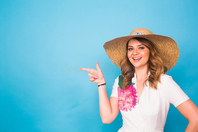 Bright studio portrait of attractive young woman pointing copyspace on blue background. stock images