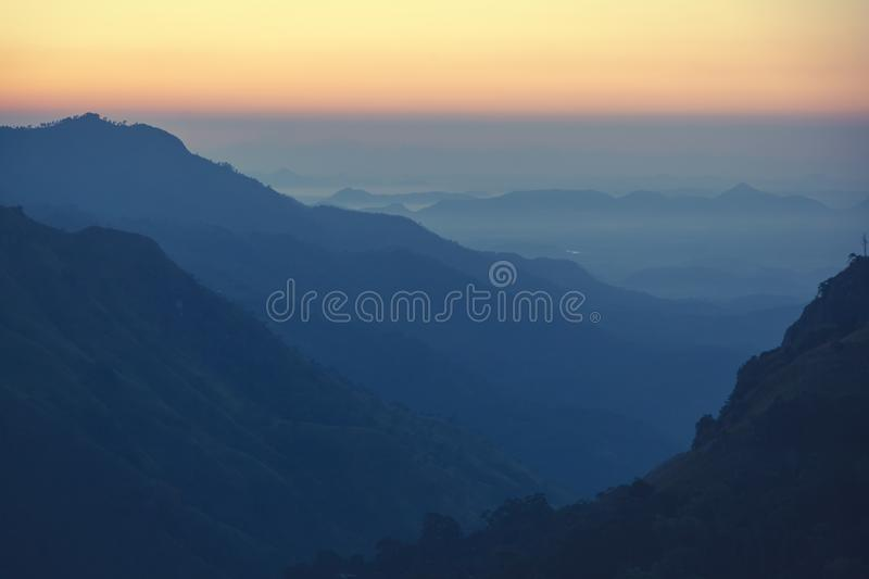 Bright stunning amazing sunset dawn in the mountains of Sri Lanka, the sun rises from behind the mountains. Beautiful minimalistic royalty free stock photo
