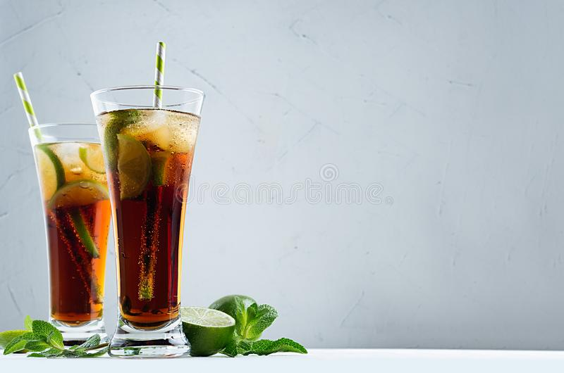 Bright summer fresh cocktail of cola with ice in two glasses with mint and lime in dark grey modern interior. stock photography