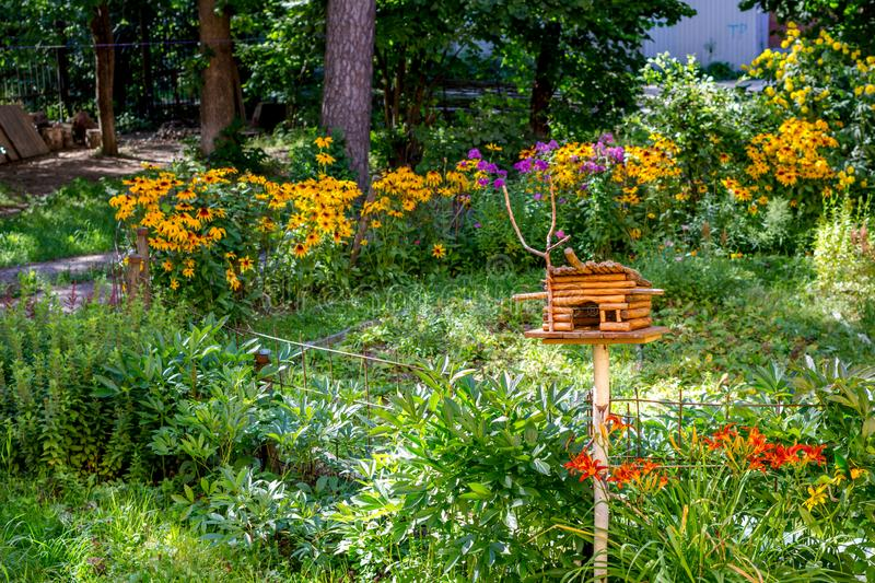 Bright summer garden with flowers and bird feeder, sunny day stock photography