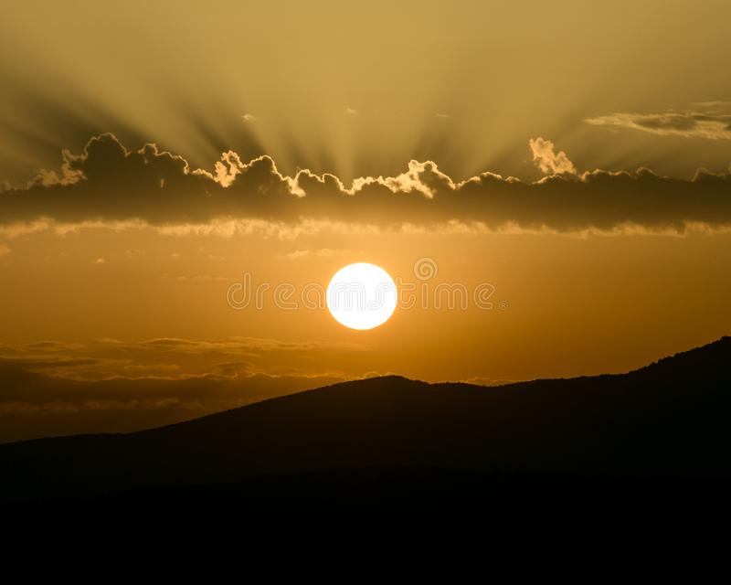 Bright summer sunrise and dramatic clouds. And sunbeams behind a dark mountain royalty free stock image