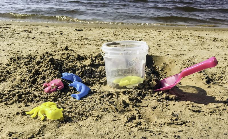 Bright summer toys on the seabeach. Plastic colored shapes, trowel and small bucket for children play with sand on the beach. Baby plastic molds lying in the stock photo