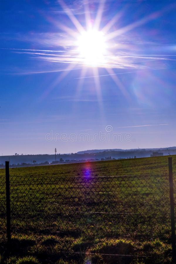 Sunset in the blue sky over the field. royalty free stock photos