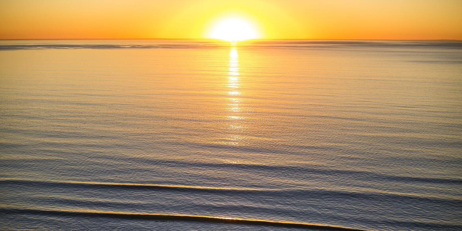 Bright sun and golden sky over the ocean at sunset stock photography