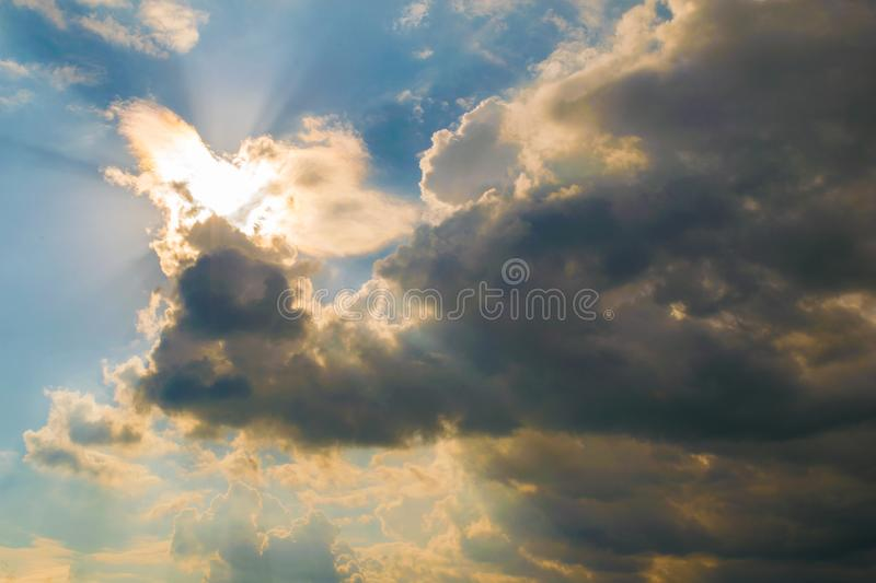 Bright sun illuminating the clouds from behind with light rays stock photography