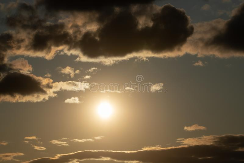 bright sun in an orange sky with dark clouds at sunset royalty free stock images
