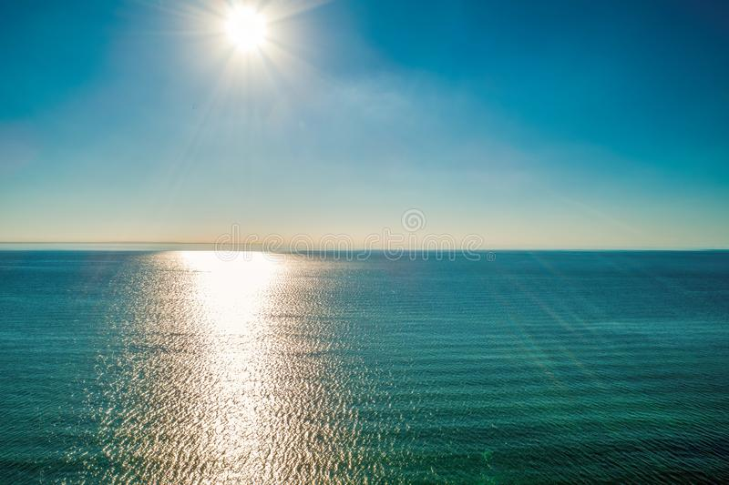 Bright sun rays over calm sea water. Bright sun rays over calm sea water - minimal aerial seascape with copy space royalty free stock image