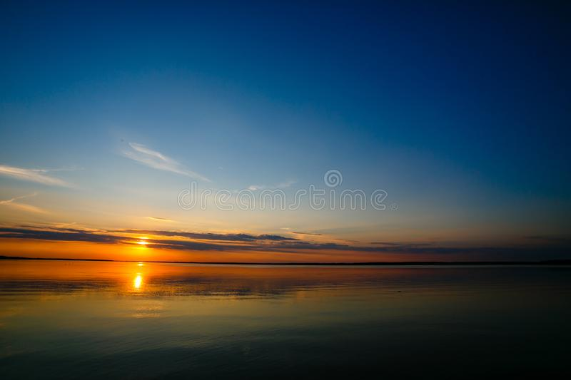 Bright sun rolling down the horizon line stock photo