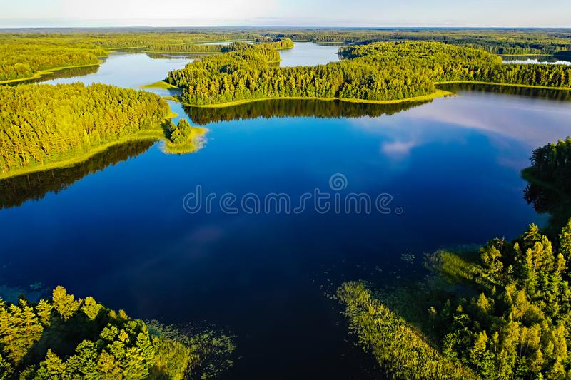 Bright sun shines above blue lakes and green forest, aerial landscape stock images