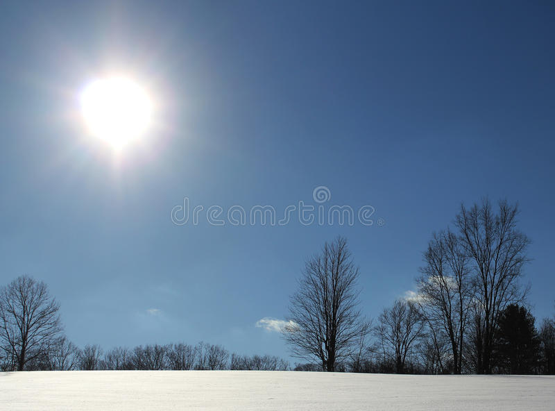 Bright sun on a snow covered hill royalty free stock photos