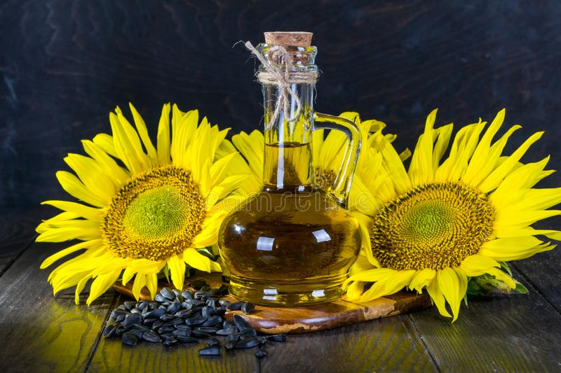 Bright sunflowers with seeds and bottle of oil on wooden table. Close up royalty free stock photo
