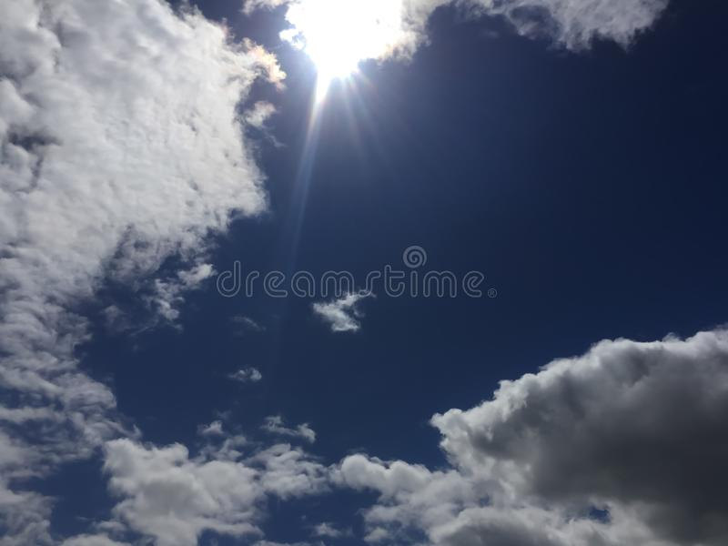 Bright sunlight against a blue sky with clouds, rays of the sun. royalty free stock image