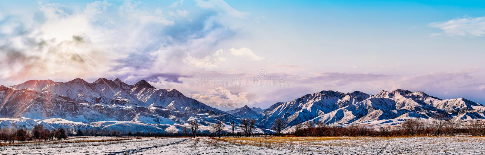 Bright sunlight through the clouds against the backdrop of a breathtaking evening, morning sky and snowy mountain peaks at sunset, royalty free stock images