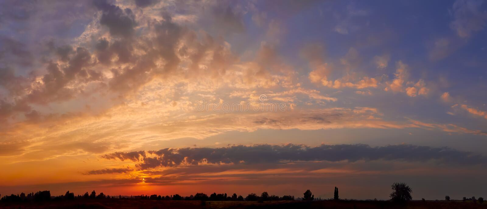 Bright sunlight through the clouds against a breathtaking evening sky at sunset. Panorama, natural composition stock photography