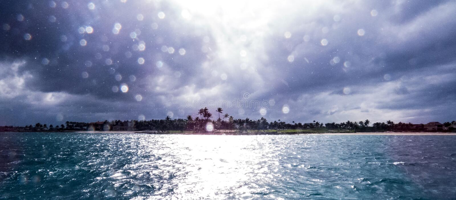 Bright sunlight coming out of the storm clouds and reflecting on droplets stock photography