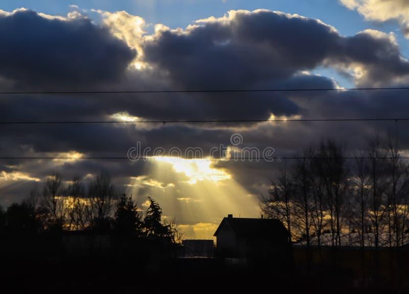 Bright sunlight through dark clouds illuminates a house in the village stock image