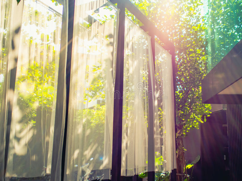 Bright sunlight through a large window. Bright sunlight streaming outdoor interior through a large window with lens flare effect stock image