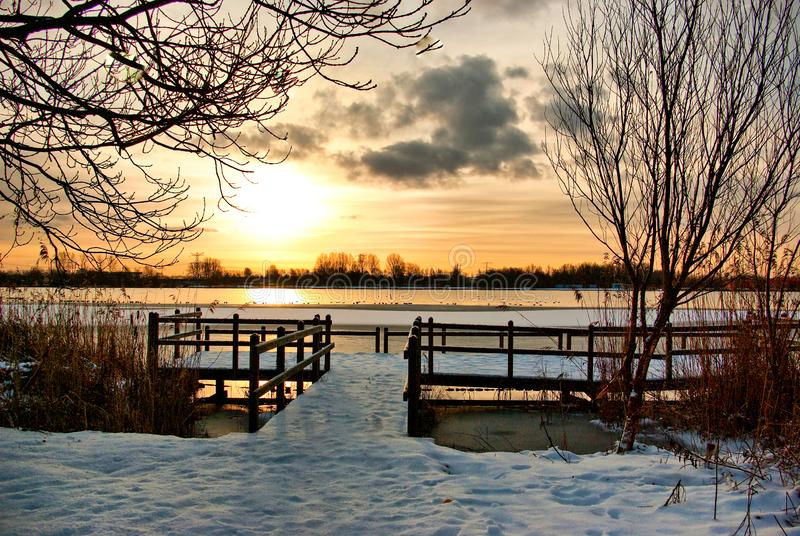 Bright sunrise at the jetty near the lake on a snowy winter morning. Bright sunrise at the jetty near Gaasperplas lake on a snowy winter morning, Gaasperplas stock photos