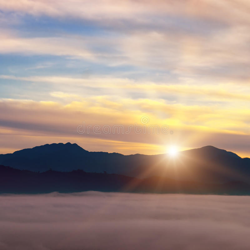 Bright sunrise, the mist in a mountain valley and mountain peaks. Bright sun rise, the mist in a mountain valley and mountain peaks on the horizon royalty free stock images