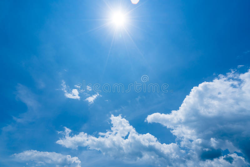 Bright sunshine with sun flares and clouds on clear blue sky background, hot summer concept stock photo