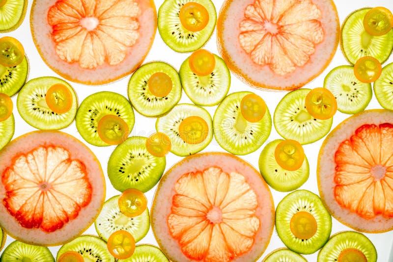 Bright sweet grapefruit, kumquat and kiwi slices on white. Bright sweet grapefruit, kumquat and kiwi slices. Juicy transparent fruit on white royalty free stock photography